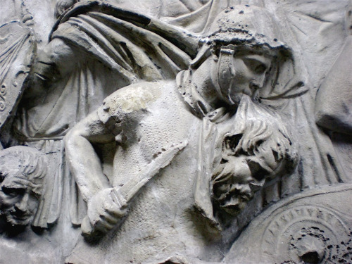 Warrior holding the head of a decapitated Dacian by the hair. Charming!